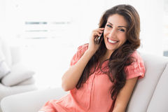 Happy brunette sitting on her couch on a phone call Royalty Free Stock Images