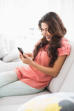 Happy brunette sitting on her couch using her smartphone Royalty Free Stock Images