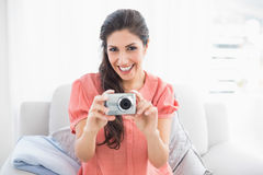 Happy brunette sitting on her sofa taking a picture of the camera Royalty Free Stock Image