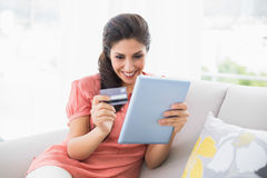 Happy brunette sitting on her sofa using tablet to shop online Stock Photos
