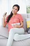 Happy brunette sitting on her sofa watching tv holding bowl of popcorn Royalty Free Stock Images
