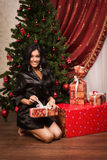 Happy brunette sitting near a Christmas tree with gifts Stock Photography