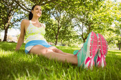 Happy brunette in sportswear relaxing on the grass Stock Photo