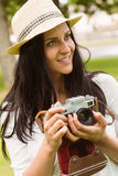 Happy brunette in straw hat holding retro camera Stock Images