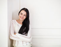 Happy brunette teen girl near the wall in the room Royalty Free Stock Images