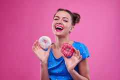 Happy brunette with two buns hair holding delicious doughnut wit Royalty Free Stock Photos