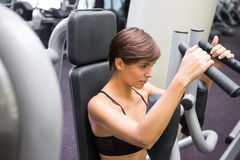 Happy brunette using weights machine for arms Stock Images