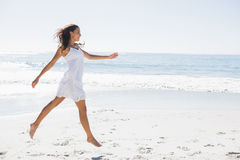 Happy brunette in white sun dress skipping on the sand Royalty Free Stock Image