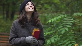 Happy brunette woman with a book smiling under a foliage