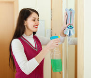 Happy brunette woman cleaning  mirror Stock Photo