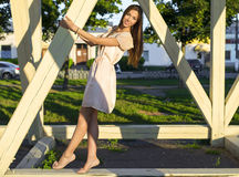 Happy brunette woman dress relaxing fun leaning on wooden piles park enjoy your vacation, fashion style urban life. Stock Images