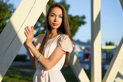 Happy brunette woman dress relaxing fun leaning on wooden piles park enjoy your vacation, fashion style urban life. Stock Photos