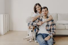 Free Happy Brunette Woman Embraces Husband With Love, Being In Good Mood, Smiles Positively. Husband, Wife And Dog Pose Together In Stock Image - 160937341