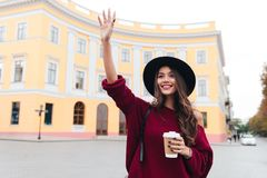 Happy brunette woman in hat and sweater waving away. And glad to meet outdoors Stock Photo