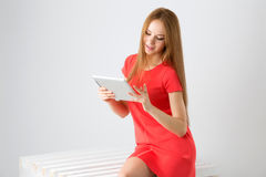 Happy brunette woman holding in hand electronic tablet touch pad computer one finger touch digital screen and smiling Royalty Free Stock Photography