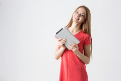 Happy brunette woman holding in hand new electronic tablet touch pad computer Stock Photography