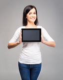 Happy brunette woman holding a tablet computer Royalty Free Stock Photo