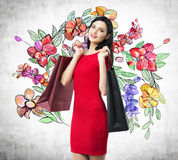 A happy brunette woman holds colourful bags from fancy shops. The concept of shopping. A sketch of different flowers is drawn on the concrete wall royalty free illustration
