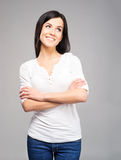 Happy brunette woman in jeans in a studio. Young and happy brunette woman in jeans in a studio Royalty Free Stock Photos