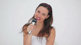 Happy brunette woman with a microphone is singing stock footage