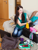 Happy brunette woman packing suitcases Royalty Free Stock Photography