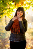 Happy brunette woman in scarf posing at autumn park Stock Photo