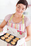 Happy brunette woman showing muffins Royalty Free Stock Photography