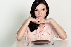 Happy brunette woman sitting in front of an empty dish, plate. Stock Photo