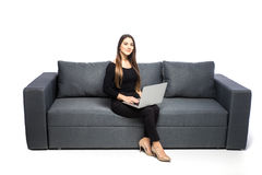 Happy brunette woman sitting on sofa with laptop on white background Royalty Free Stock Image