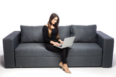 Happy brunette woman sitting on sofa with laptop on white background Stock Photos