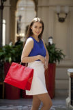 Happy brunette woman with some red shopping bag. Young beautiful brunette woman with some red shopping bag in the mall Royalty Free Stock Images