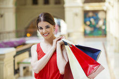 Happy brunette woman with some red shopping bag. Young beautiful brunette woman with some red shopping bag in the mall Stock Images