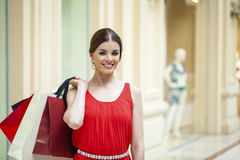 Happy brunette woman with some red shopping bag. Young beautiful brunette woman with some red shopping bag in the mall Stock Photo