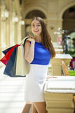 Happy brunette woman with some red shopping bag. Young beautiful brunette woman with some red shopping bag in the mall Stock Image