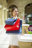 Happy brunette woman with some red shopping bag. Young beautiful brunette woman with some red shopping bag in the mall Royalty Free Stock Photos