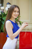 Happy brunette woman with some red shopping bag. Young beautiful brunette woman with some red shopping bag in the mall Stock Photography
