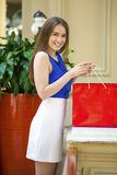 Happy brunette woman with some red shopping bag. Young beautiful brunette woman with some red shopping bag in the mall Stock Photos