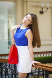 Happy brunette woman with some red shopping bag. Young beautiful brunette woman with some red shopping bag in the mall Royalty Free Stock Photography