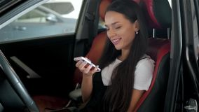 Happy brunette woman student in modern business class car with phone use applications for travellers. Happy brunette woman student in modern business class car stock video