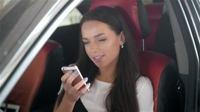 Happy brunette woman student in modern business class car with phone use applications for travellers. Happy brunette woman student in modern business class car stock footage