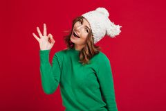Happy brunette woman in sweater and funny hat showing ok stock photos