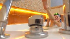 Happy brunette woman takes foamy bath and scrubs her leg. 4K shot stock video