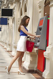 Happy brunette woman withdrawing money from credit card at ATM Royalty Free Stock Image