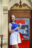Happy brunette woman withdrawing money from credit card at ATM Stock Photography