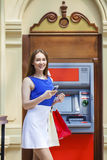 Happy brunette woman withdrawing money from credit card at ATM Stock Images