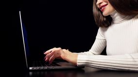 Happy brunette woman working on her laptop against black background. 4K shot stock video footage