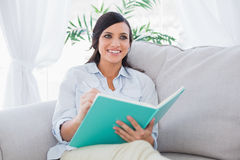 Happy brunette writing while sitting on the sofa Stock Images
