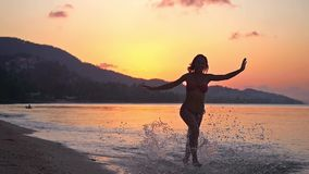 Happy brunette young woman running in tropical beach at amazing sunset in slow motion. 1920x1080 stock video footage
