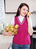 Happy brunnette girl holding  heap of pears Royalty Free Stock Photo