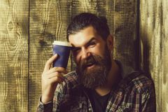Happy brutal man smiling with blue plastic cup. Happy brutal man or bearded caucasian hipster with grey hair, long beard and moustache smiling with blue plastic royalty free stock photos